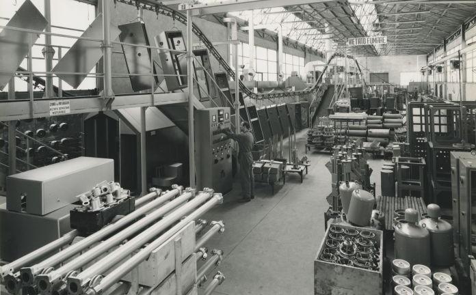 Battaglia Terme, 1968. Veduta d'insieme del reparto verniciatura delle Officine Elettromeccaniche  Galileo  S.p.a., con un  operaio  che agisce  su  di  un pannello di controllo (Foto dall'Archivio Edison presso il Centro per la cultura d'impresa)
