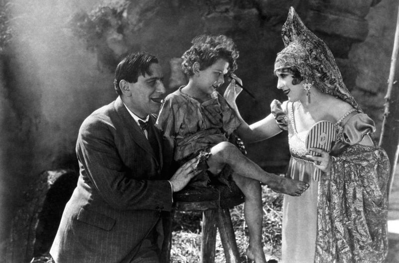 1925: Dir. Ernst Lubitsch, w. trademark cigar in his mouth, watching as actress Pola Negri, in costume, puts makeup on unident. boy actor.