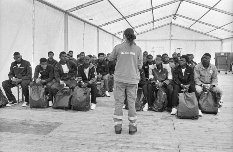 Un'operatrice della Croce Rossa spiega l'organizzazione del centro Fenoglio a rifugiati richiedenti asilo appena arrivati nella struttura, Settimo, 13 maggio 2017