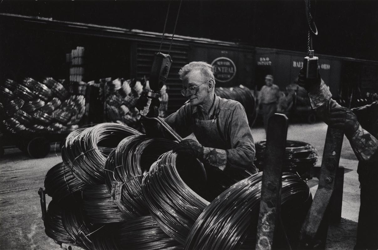 W. Eugene Smith, USA, 1918-1978 Operaio di un'acciaieria che prepara le bobine / Mill Man Loading Coiled Steel, 1955-1957 Stampa ai sali d'argento / gelatin silver print 22.86 x 34.61 cm Gift of the Carnegie Library of Pittsburgh, Lorant Collection. © W. Eugene Smith / Magnum Photos