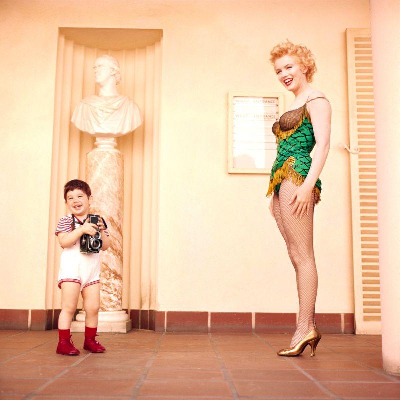 Il figlio del fotografo Milton H. Greene, Joshua, con al collo la macchina fotografica, gioca con Marilyn Monroe durante il servizio pubblicitario realizzato dal padre per il film Fermata d'autobus. Foto di Milton H. Greene.© 2018 Joshua Greene archiveimages.com