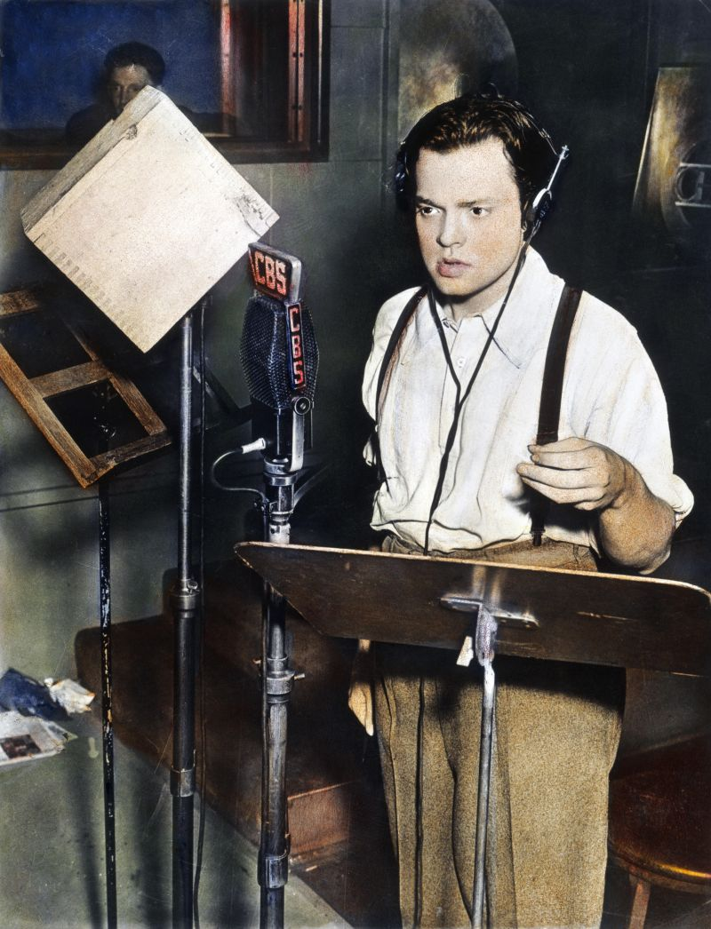 FF9YAP ORSON WELLES (1915-1985). /nAmerican director, producer, screenwriter, and actor. Shown broadcasting his famous adaptation of H.G. Wells' novel 'The War of the Worlds,' 30 October 1938. Oil over a photograph.