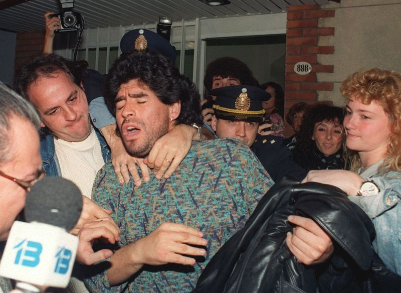 (FILES) Argentinian soccer player Diego Maradona (C) is removed by police from a Buenos Aires apartment, 26 April 1991, after being arrested for possession of half-kilo of cocaine. Maradona was suspended by the Italian League 29 March 1991, after an analysis of his urine tested positive for cocaine. (Photo by DANIEL LUNA / AFP) (Photo credit should read DANIEL LUNA/AFP/Getty Images)
