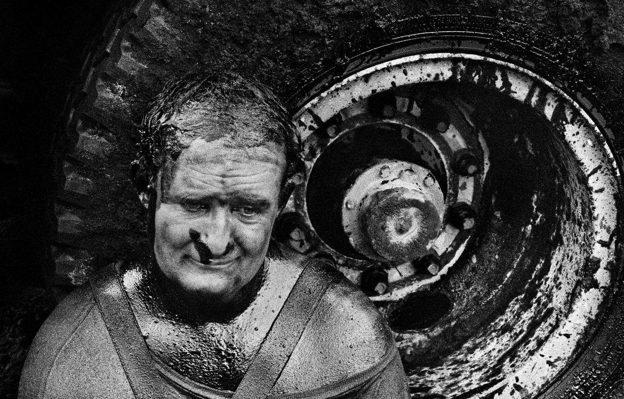 SEBASTIÃO SALGADO Il Kuwait dopo la fine della Guerra del Golfo - I pozzi petroliferi continuano a bruciare, causando un massiccio disastro ecologico e una grande perdita di denaro. Compagnie di pompieri specializzati, provenienti da tutto il mondo, a lavoro per estinguere il fuoco. Operaio della Safety Boss Company durante una pausa, 1991 © Salgado/AmazonasImages/Contrasto