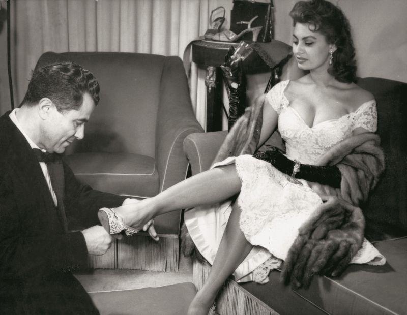 Sophia Loren e Salvatore Ferragamo fotografati insieme durante la serata presso l'Open Gate Club di Roma, organizzata per celebrare il suo nuovo brevetto della pelle di leopardo marino, 28 febbraio 1955. Ferragamo prova una scarpa in merletto all'attrice. © Museo Salvatore Ferragamo