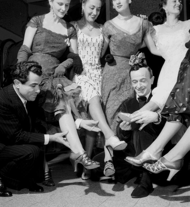 La sfilata di modelli e abiti a Palazzo Spini Feroni del 1951. Le modelle indossano i sandali Kimo, invenzione di Ferragamo. In basso Salvatore Ferragamo e il sarto romano Emilio Schuberth, autore degli abiti. © Museo Salvatore Ferragamo, Foto David Lees