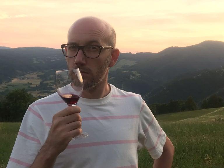 Un bellissimo panorama collinare al tramonto sovrasta il primo piano del regista del film